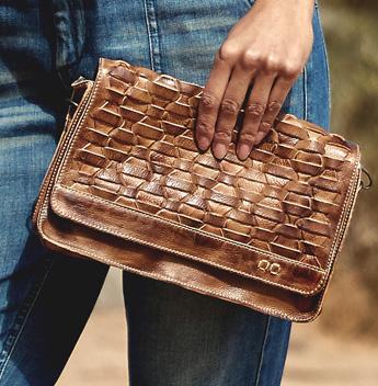 Hand holding handwoven tan Aruba clutch bag against denim