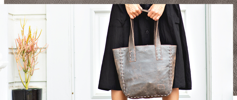 Woman with black skirt holding distressed silver leather mid size Stevie Tote bag next to a plant
