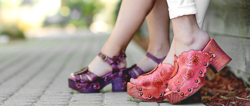 A pink and purple Anna Sui hand tooled leather sandals worn and leaning up against a concrete wall