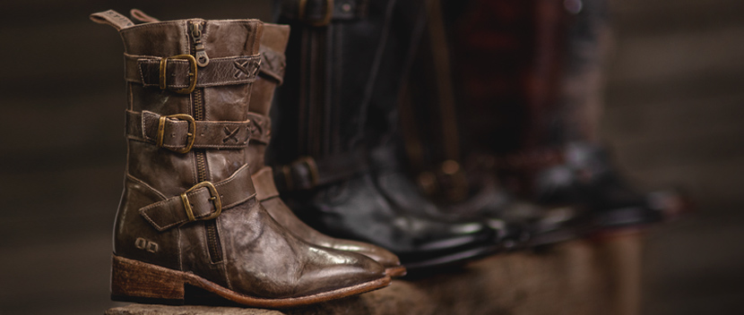 Close up of brown leather boots with buckles against a dark background.