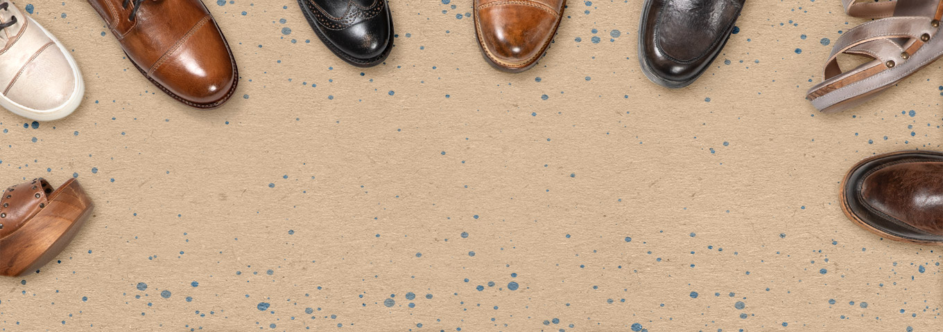 6 toes of shoes spread evenly at the top on tan kraft paper with blue ink spatters