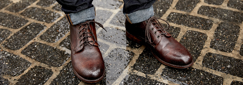 Mens Teak Bradley Boot, a goodyear welted 5 eye plain toe chukka boot on wet concrete pavers