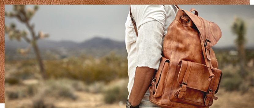 Man with Jackson Tan Driftwood leather drawstring backpack in the desert