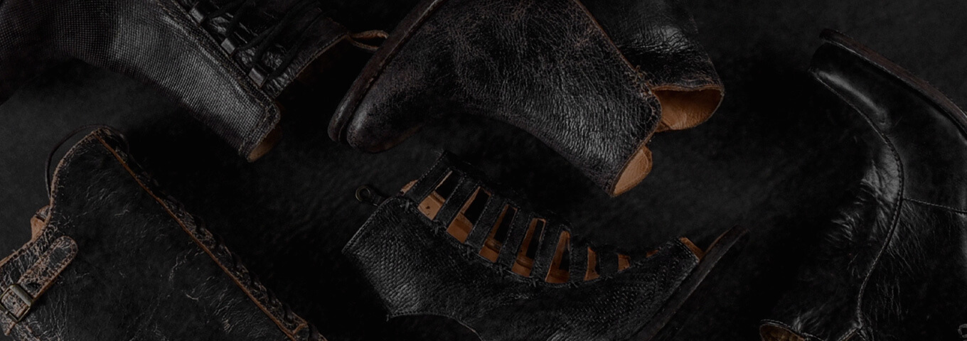 Black leather shoes laid out against a black background