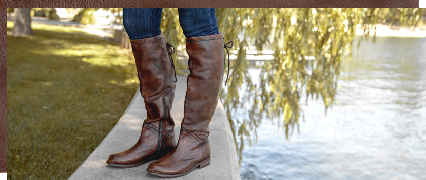 Womens knee high Teak Manchester S boot with back laces, worn with denim by a lake